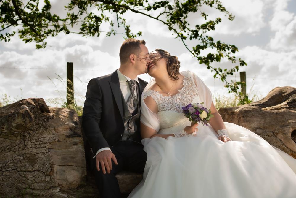 mariés qui s'embrassent sur un tronc d'arbre